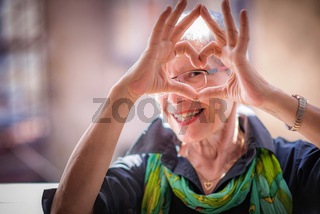 Senior woman making a heart shape, cute and lovely
