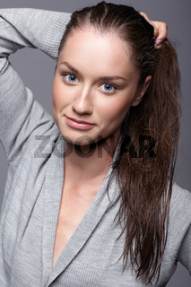 Beauty portrait of young woman in gray dress. Brunette girl with bright blue eyes and day female makeup
