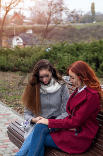 Female teenagers discussing a book sitting on the bench in an autumn city park