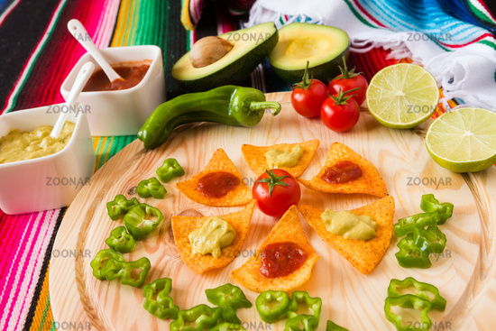 Nachos chips and vegetables on a chopping board