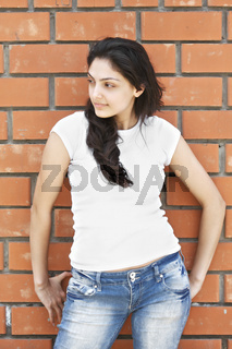 Young brunette at brick wall