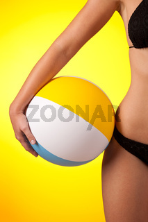 Part of female body wearing black bikini  and holding beach ball