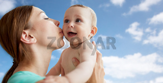 happy mother kissing little baby over blue sky