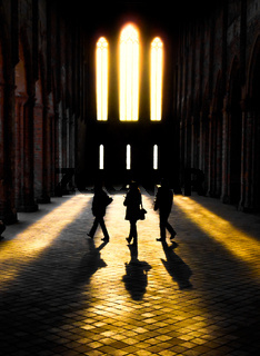 Silhouttes of three people walking through sunlight in an ruin of an old monastery