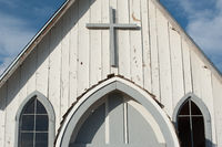 Front of a early wooden American church in the country with a cross and arched windows.