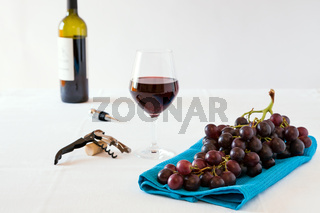 Bunch of red grapes and a glass of red wine with a wine bottle