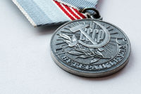 Silver colored Russian veteran war medal with soviet hammer and sickle on a white surface