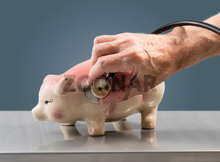 Senior male hand holding stethoscope on piggy bank