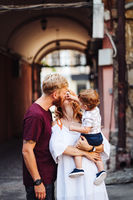 Happy parents playing with little son outdoor