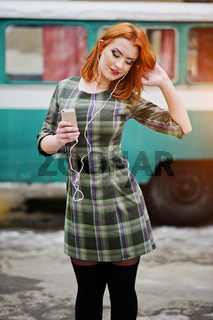 Young red haired girl lady with mobile cell phone and headphones, wearing on checked dress background old vintage turqoise minivan bus.