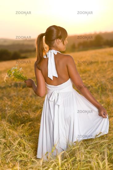 Romantic brunette woman in sunset corn field