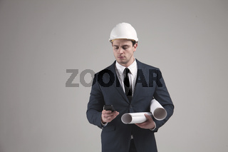 Portrait of a engineer in white helmet on gray background