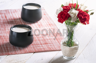 Flowers in a vase and cups with milk