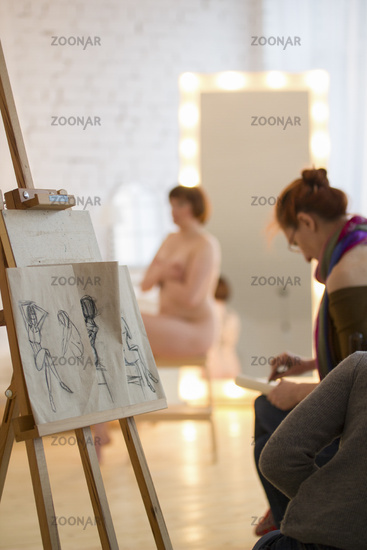 Artists sketching a nude model in drawing class