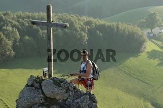 Mann am Gipfel mit Gipfelkreutz