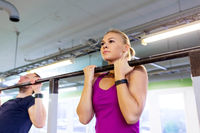 couple doing pull-ups at horizontal bar in gym
