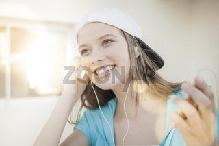 Junge froehliche Frau mit MP3 Player und Ohrhoerer