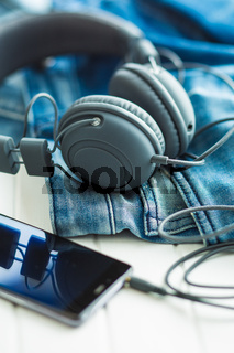 Headphones, cellphone and blue jeans.