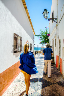 Woman in blue shirt walking on the narrow streets of Albufeira, Portugal.