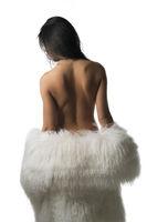 Nude brunette in luxurious fur coat rearview