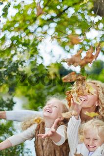 Kinder und Mutter werfen Blätter in die Luft