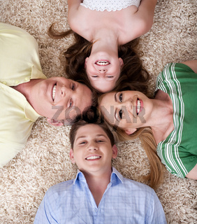 Portrait of happy family lying on carpet with their heads close together and smiling.