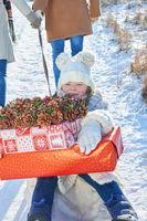 Kind sitzt mit Geschenken auf einem Schlitten