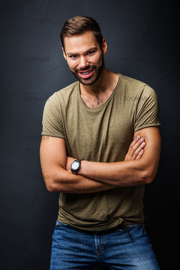 Handsome man smiling, standing confident with crossed arms