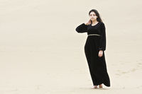 Serious woman going in sands