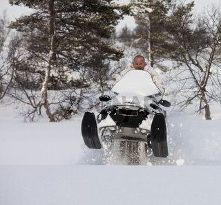 Man driving snowmobile and jumping in the snow, square image