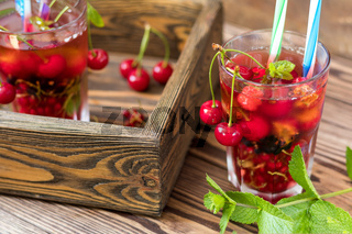 Glasses of refreshing  drink flavored with fresh fruit and decorated with cherries covered with dew drops. Wooden background
