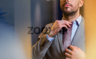 close up of man trying tie on at mirror