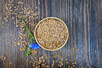Flaxen brown seed in bowl with flower on board top