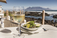 White wine and oysters infront of table Mountain , Bloubergstrand