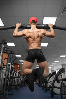 A male bodybuilder performs pull-ups on a horizontal bar in the gym.