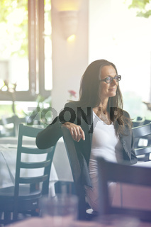 Thoughtful and pretty young woman sitting in a restaurant