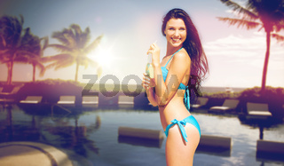 happy woman with bottle of drink on summer beach