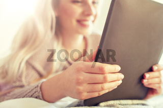 close up of young woman with tablet pc at home