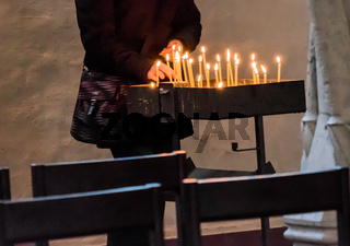 Light a candle in a Christian church to commemorate the deceased.