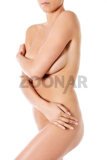 Topless woman covers her breasts with hands.