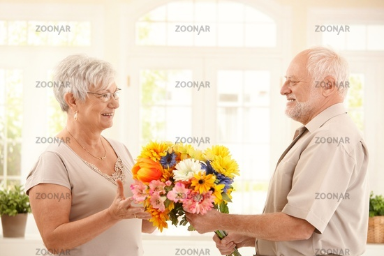 Senior man bringing flowers to wife
