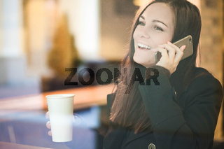 Woman with smartphone drinking coffee.