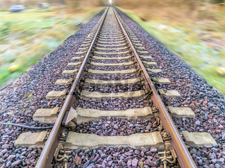 Abstract post-processed photograph of railroad tracks with blurred landscape, central perspective