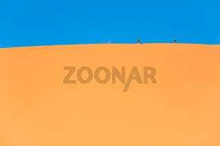 Traveler in the desert, active couple trekking in hot sandy wilderness