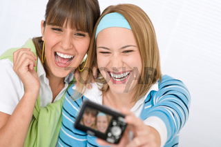 Two young cheerful woman taking picture