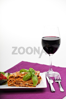 lasagna al forno on a plate with red wine