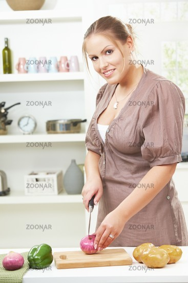 Young woman chopping onion