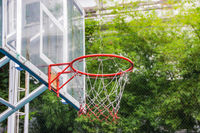 Basketball hoop in the park with green trees as background.