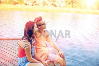 happy teenage couple hugging on river berth