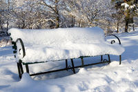 Park bench seat covered in lots of snow.
